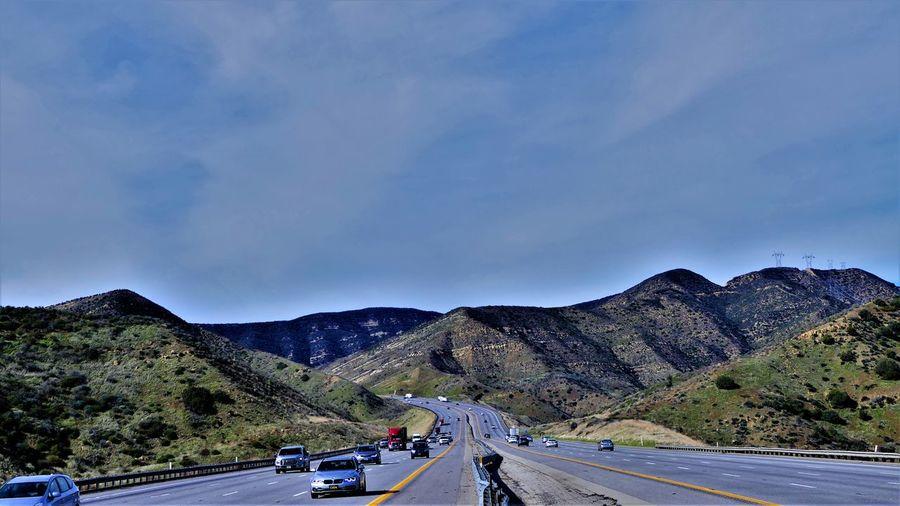 Vehicles on road against mountain range