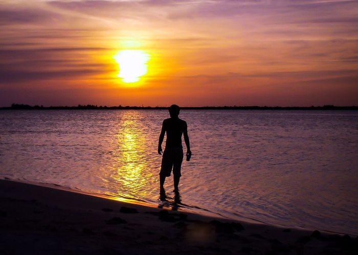 Rear View Of Silhouette Man Standing On Lake Against Sky During Sunset