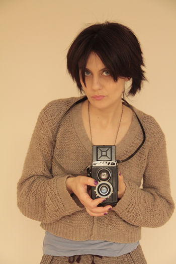 Portrait of woman photographing while standing against beige background