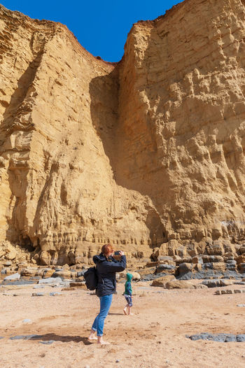 Rear view of mother photographing son while standing against rock formation