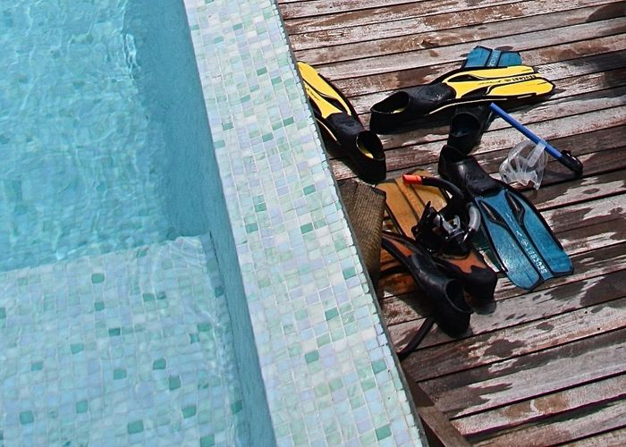 High Angle View Of Diving Flippers On Boardwalk By Swimming Pool