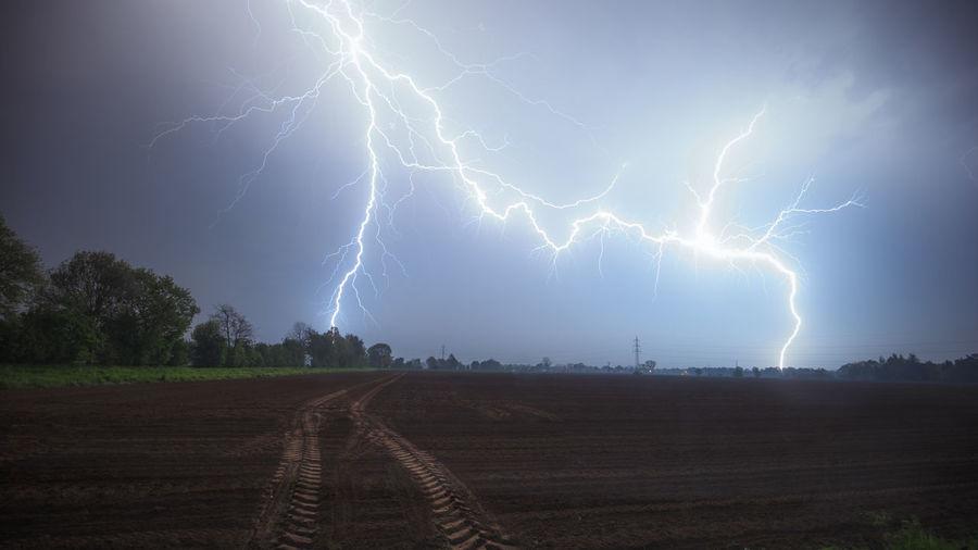 Lightning over landscape against sky at night