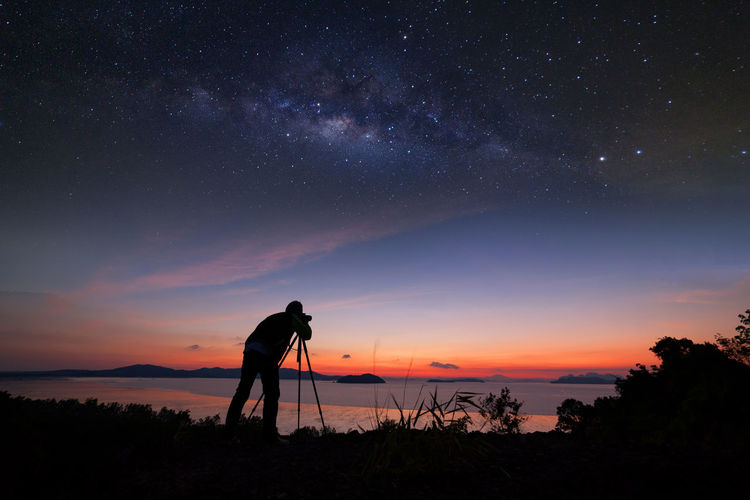 Astronomy Beauty In Nature Idyllic Land Leisure Activity Lifestyles Men Milky Way Nature One Person Outdoors Photographer Photography Themes Real People Scenics - Nature Silhouette Sky Standing Star - Space Sunset Tranquil Scene Tranquility Tripod