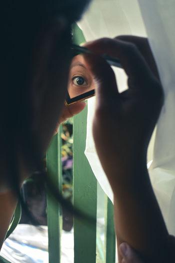 Portrait of woman holding window