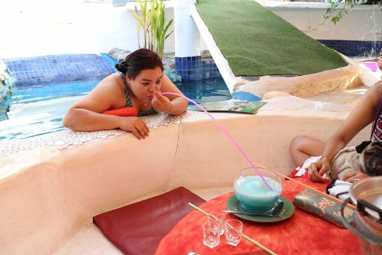 Woman in pool having drink with long drinking straw