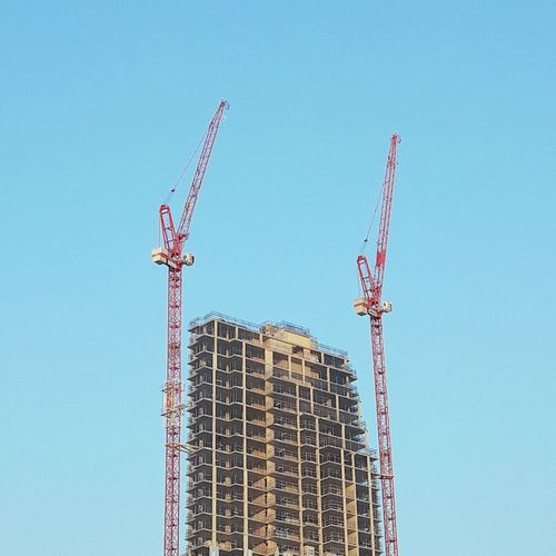 Low angle view of cranes at under construction site against clear blue sky