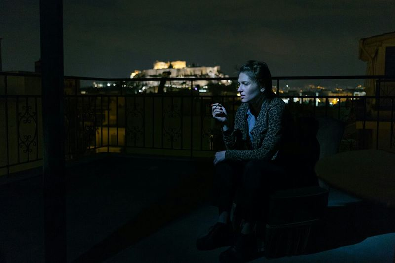 Woman sitting in illuminated building against sky at night