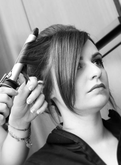 Cropped hands of beautician styling woman hair