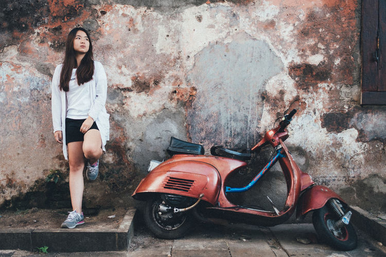 Young woman standing by motor scooter against wall