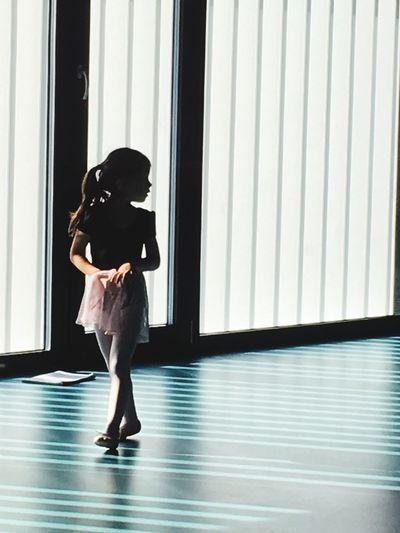 Full length of ballerina walking in ballet studio
