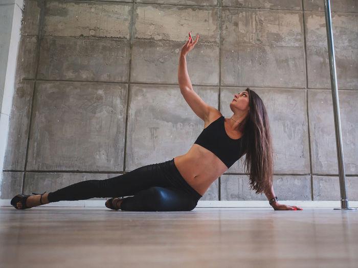 Sensuous woman dancing while lying on floor