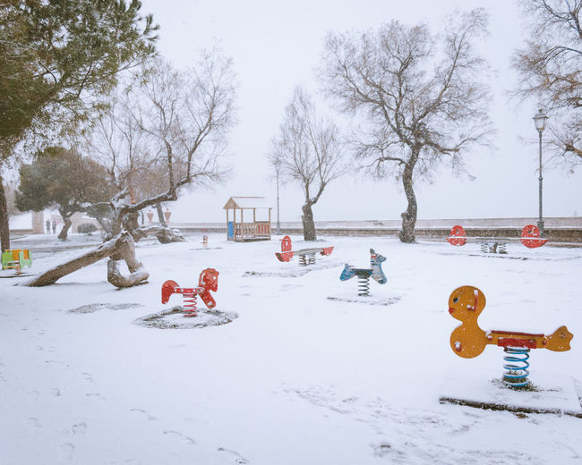 Bare Tree Beauty In Nature Childhood Cold Temperature Day Field Leisure Games Nature No People Outdoor Play Equipment Outdoors Park - Man Made Space Playground Playing Sky Snow Tobogganing Tree Weather Winter