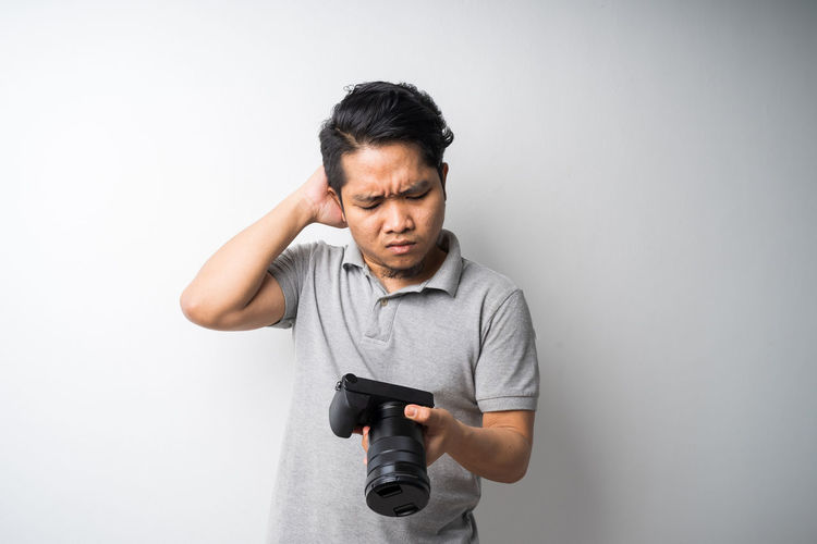 Young man holding camera against white background