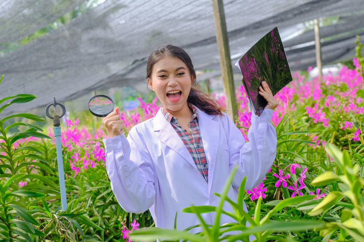 Portrait of smiling woman standing by flowering plants