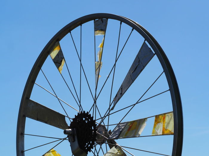 Low angle view of wheel against clear blue sky