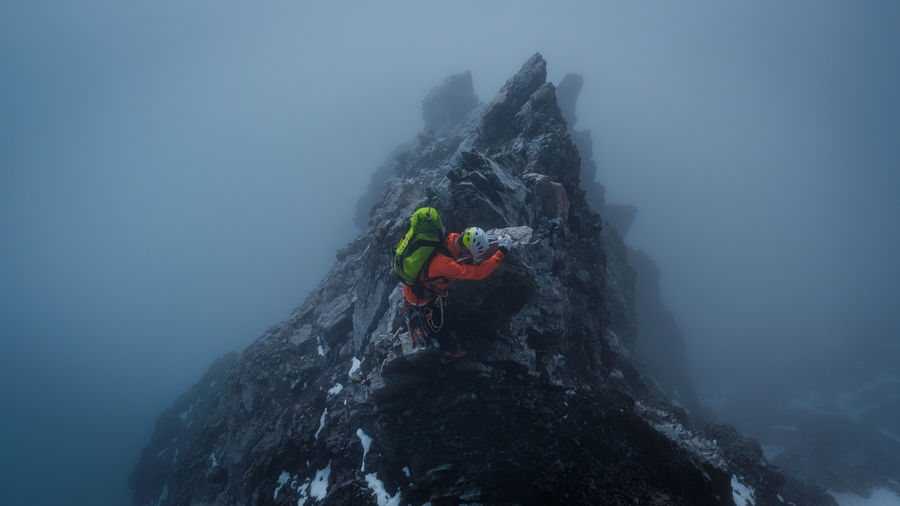 High angle view of person on rock in mountains during winter