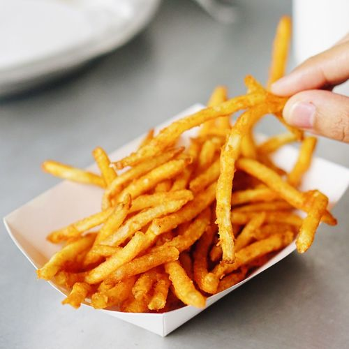 Cropped hand holding fried potatoes