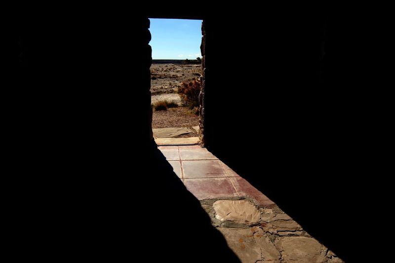 Natural light shining through a stone doorway in the desert Mysterious Contrast Interior Painted Desert Architecture Built Structure Nature Sunlight Shadow Day The Past History No People Outdoors Silhouette Building Sky Wall Copy Space Dark Old The Way Forward Wall - Building Feature