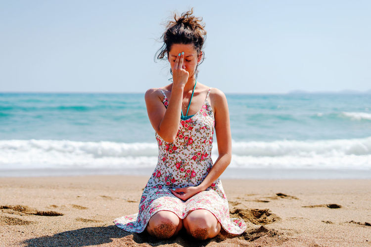 Woman praying while sitting at beach against sky