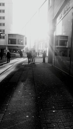 Shadow of man on road in city