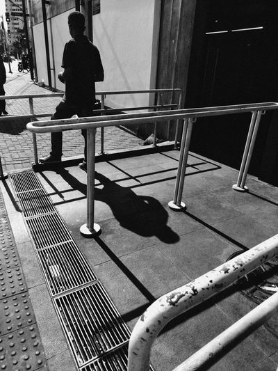 Rear view of person sitting on railing