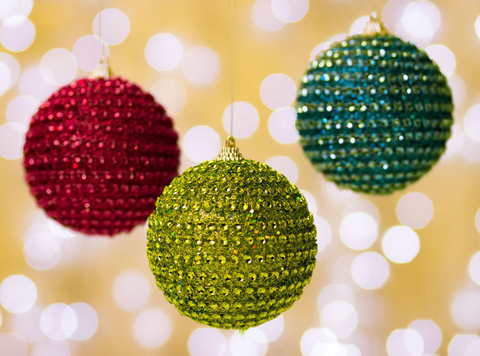 Close-up of christmas ornaments hanging against illuminated light