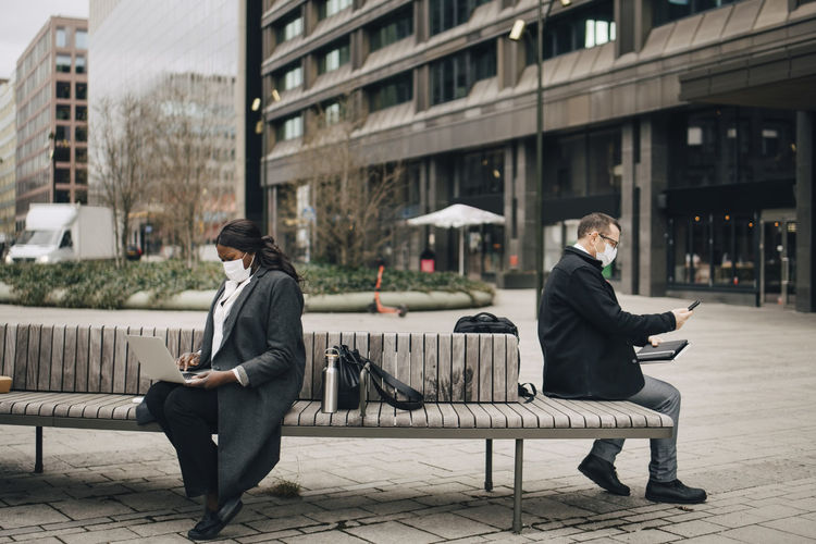 Full length of couple sitting on bench in city