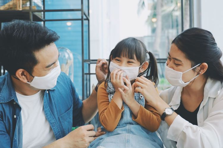 Close-up of smiling family wearing flu mask sitting at home