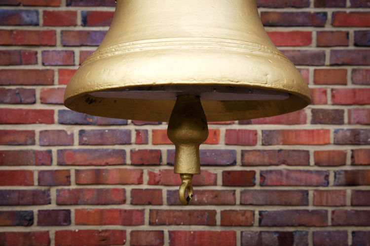 Low angle view of electric lamp against brick wall