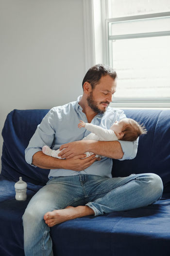Father sitting with baby girl on sofa