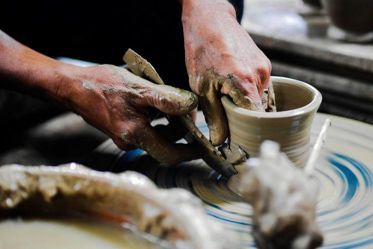 Cropped image of man molding shape on pottery wheel