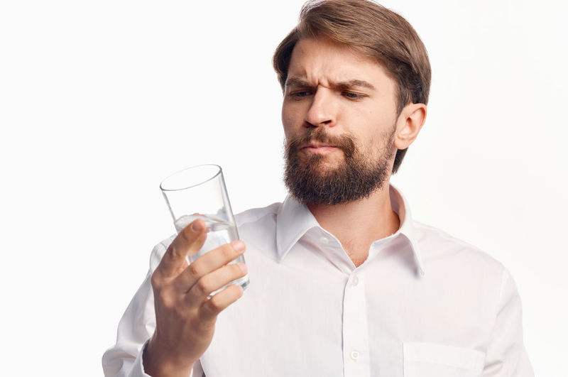 Portrait of man holding glass over white background