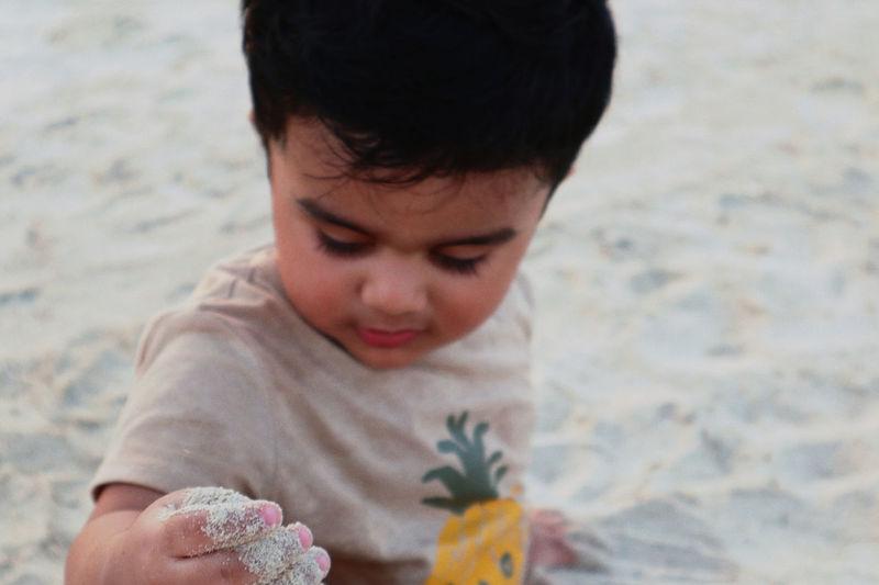 Cute boy on sand at kite beach