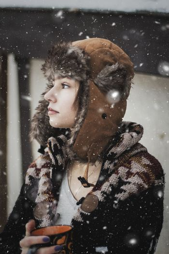 Portrait of beautiful young woman standing in snow