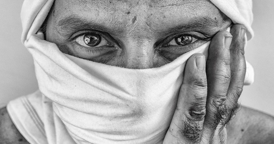 Portrait of man covering face with fabric