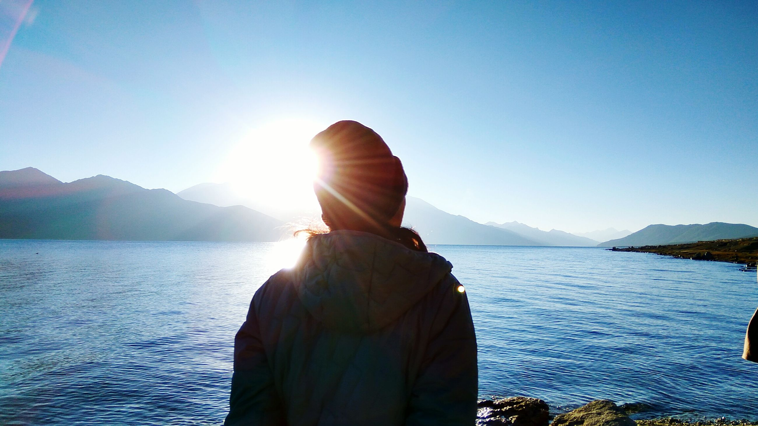 rear view, sunlight, water, reflection, lens flare, one person, blue, mountain, adults only, sky, sunbeam, nature, adult, leisure activity, only women, tranquility, beauty in nature, clear sky, day, one woman only, lake, people, real people, sun, outdoors
