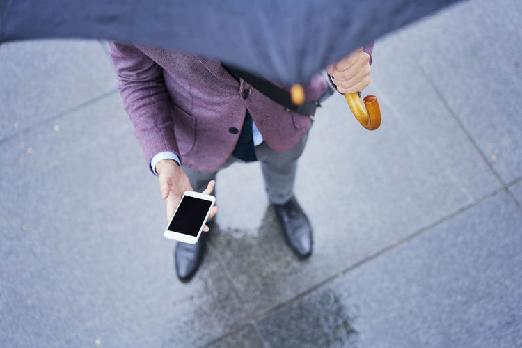 Low section of person using smart phone on footpath
