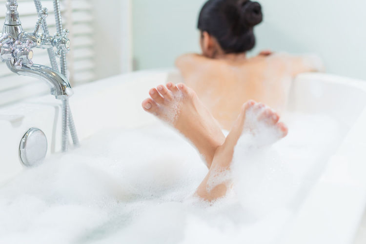 Woman relaxing in bathtub Adult Bathroom Bathtub Beautiful Woman Body Care Bubble Bath Cleaning Domestic Bathroom Domestic Room Home Hygiene Indoors  Leisure Activity Lifestyles Luxury One Person Rear View Relaxation Soap Sud Taking A Bath Washing Women