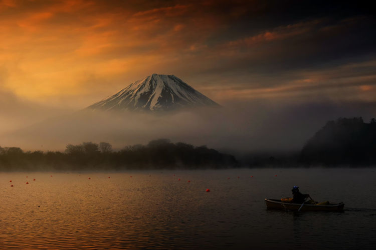 Silhouette photo of fisherman sailing boat to fishing at Lake Shoji in morning at sunrise and heavy mist in Yamanashi Prefecture, Japan. Mountain Fuji or Fujisan view at dawn background. Fujisan Morning Travel Twilight Boat Fisherman Fishing Fog Fuji Lake Mist Mountain Sail Sailing Scenics Shoji Sunrise