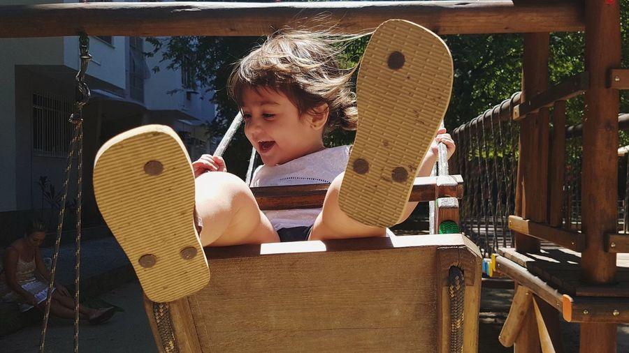 Cheerful Baby Girl Sitting On Swing