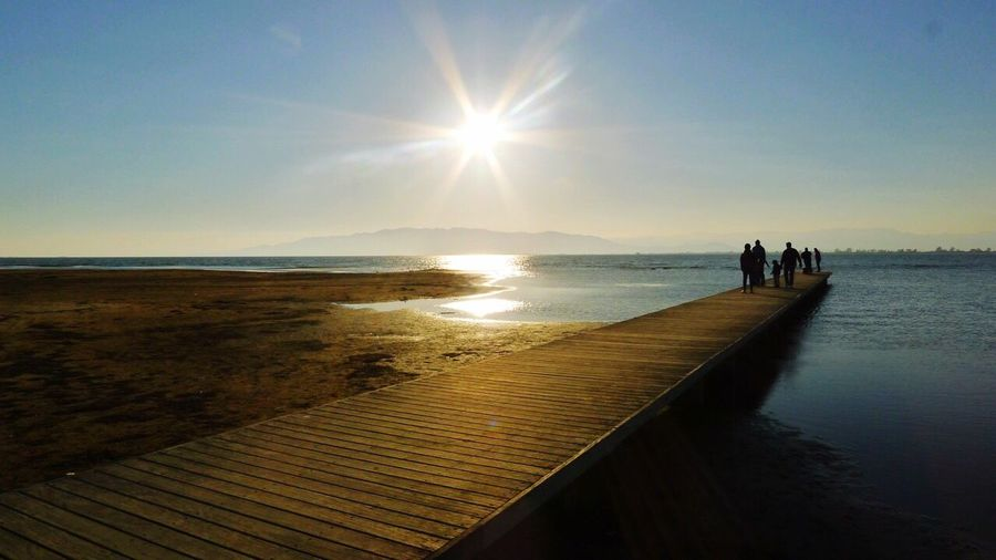 Sea Beach Water Sunlight Sky Horizon Over Water Nature Sand Scenics Real People Sun Beauty In Nature Men Two People Leisure Activity Women Tranquil Scene Outdoors Lifestyles Tranquility Dock Dockinthewater Sunset Dog Silouette