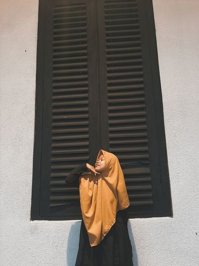 Woman wearing hijab standing by window outdoors