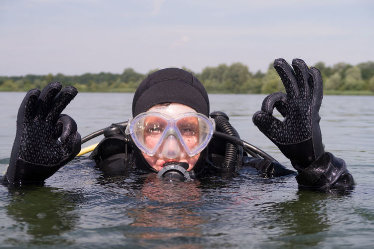 Portrait of scuba diver with ok sign in lake