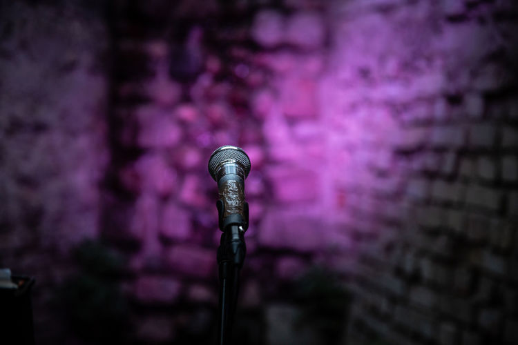Close-Up Of Microphone Against Illuminated Purple Wall