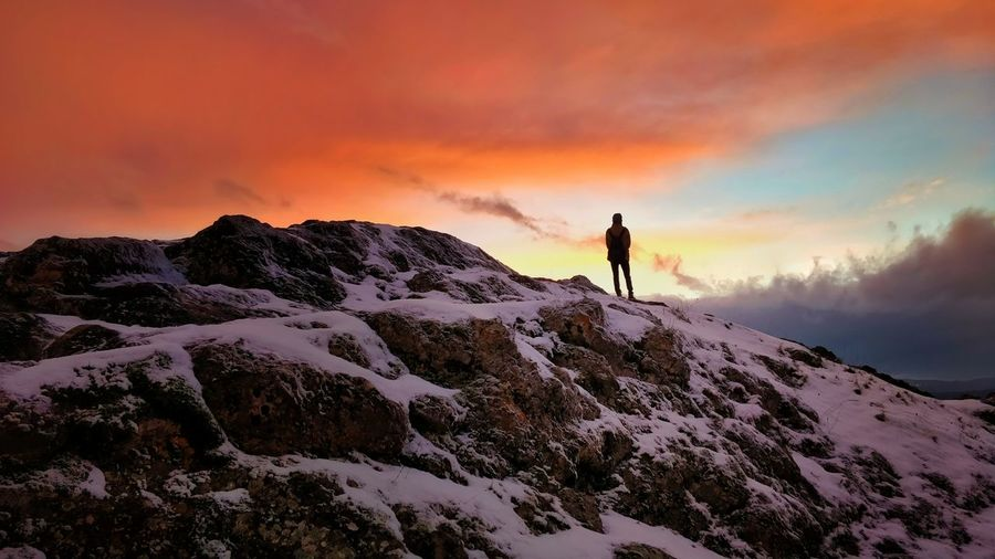 Rear view of young man standing on snow covered mountain against cloudy sky during sunset