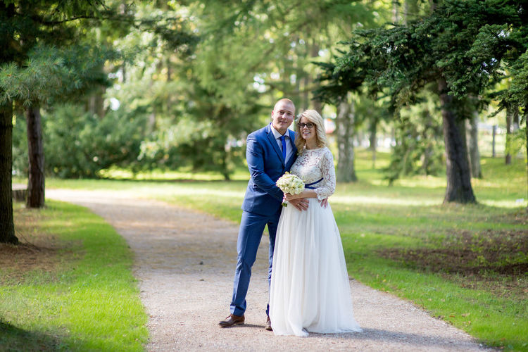 Full Length Portrait Of Bride And Bridegroom Standing On Footpath At Park