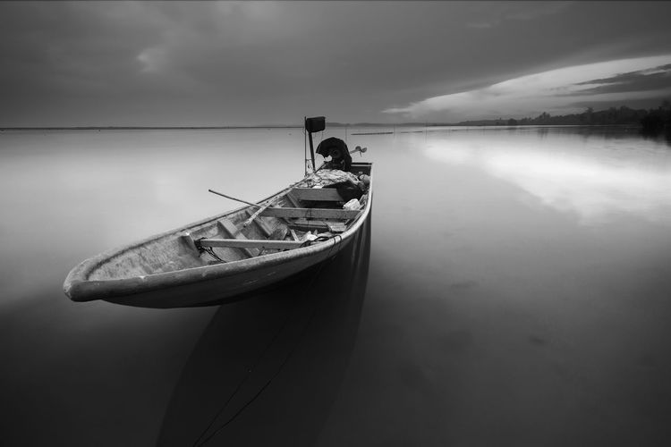 Boat Moored On Sea Against Cloudy Sky