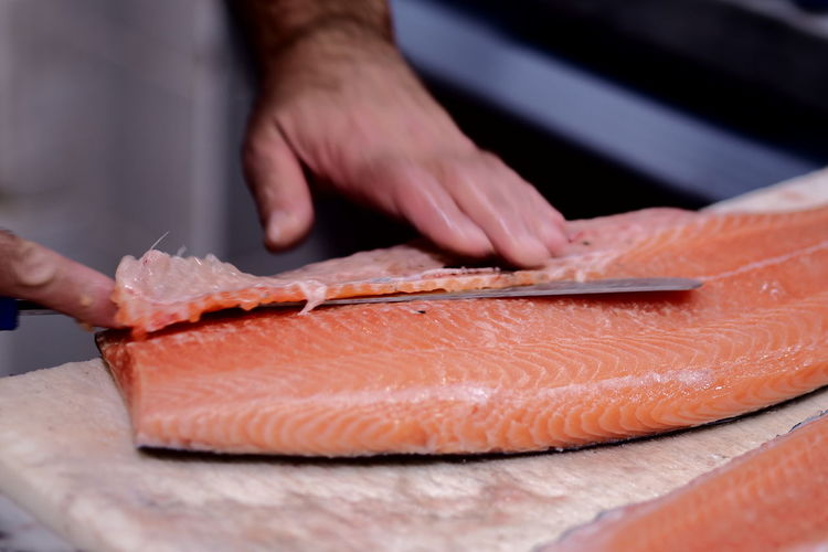 Cropped hands slicing salmon