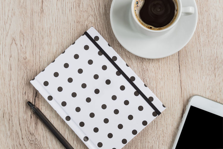 Business concept black and white polka dot cover notebook, smartphone and cup of black coffee