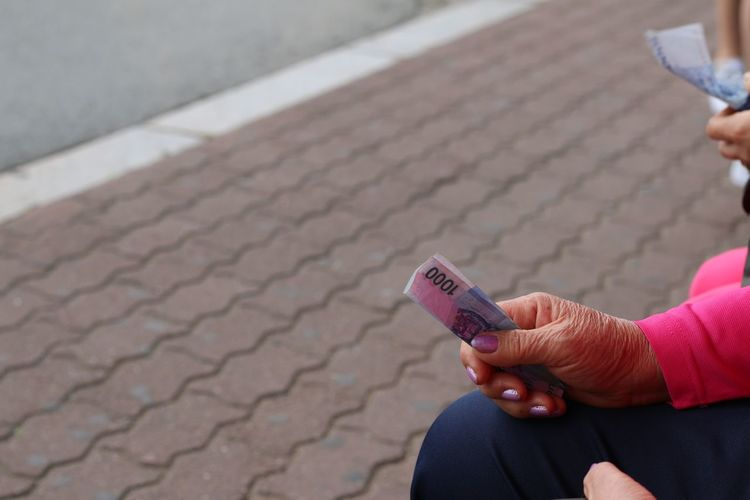 Cropped Image Of Woman Holding Paper Currency On Footpath